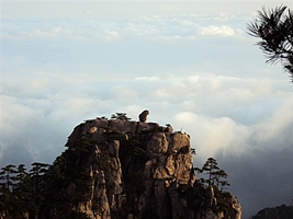 A rock balances precariously atop a karst peak before a backdrop of clouds at Huangshan (黄山, Yellow Mountain), China
