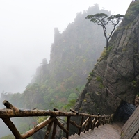 A stairway descends precipitously down the cliffside at Huangshan (黄山, Yellow Mountain), China