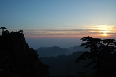 The rising sun peeks through distant clouds, making silhouettes of the trees and mountains of Huangshan (黄山, Yellow Mountain), China
