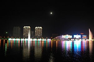 A brightly lit bank of the Songhua River at night, with tall buildings and fountains, in Jilin (吉林市), China