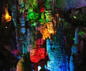 Limestone formations illuminated with multicolored lights in Yunnan's Jiuxiang Caverns