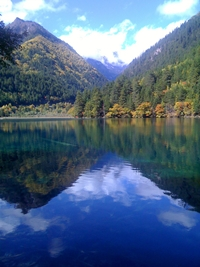 Mountains and sky reflect off the surface of a pristine blue lake in Jiuzhaigou (九寨沟), Sichuan Province, China
