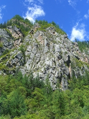A vertical view of blue sky and white, wispy clouds over a rocky cliff face in Jiuzhaigou (九寨沟), Sichuan Province, China