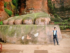 A tourist stands next to a giant foot of the Leshan Giant Buddha (乐山大佛) in Sichuan Province, China