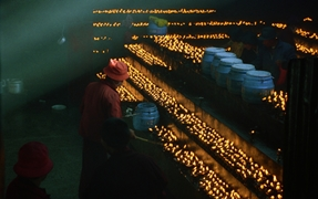 A dark room filled with long rows of yak butter candles in Lhasa (拉萨), Tibet, China