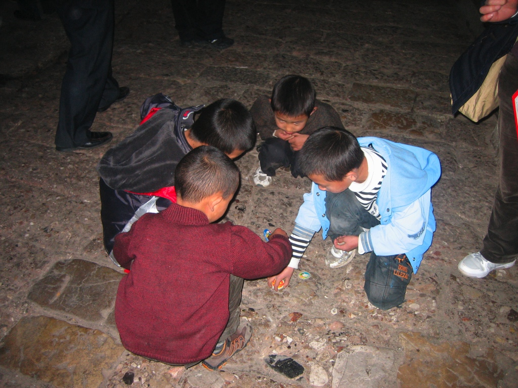 A group of boys playing a game on the street in Dayan Town