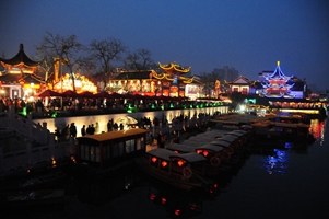 Boats line the brightly lit bank of the Qinhaui River at Nanjing's Confucius Temple at night