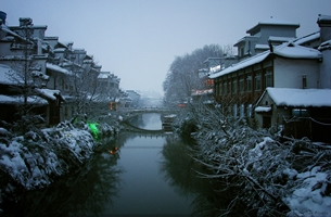 Snow-covered buildings and trees line a canal in Nanjing, China