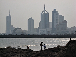 People silhouetted against the water with Zhan Bridge and the tall buildings of downtown Qingdao (青岛), China, in the background