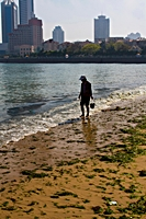 A beachcomber strolls along a beach near downtown Qingdao (青岛), China