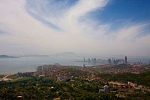 A seaside vista of blue sky and water, green trees, and urban scenery in Qingdao (青岛), China