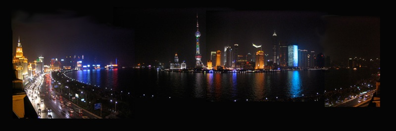 A panoramic night view across the Huangpu River at the brightly lit skyscrapers of Pudong in Shanghai, China