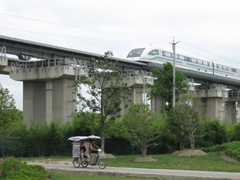 A pedicab drives under the Maglev Train line in Shanghai, China