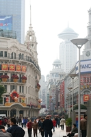 Crowds of shoppers walk along a pedestrian street section of Nanjing Road lined with tall buildings in Shanghai, China