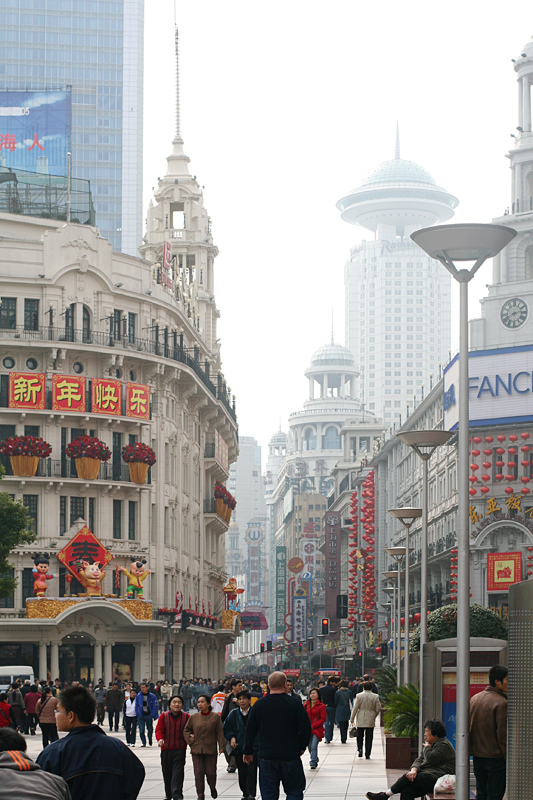 Tall buildings and crowds of shoppers on the pedestrian street section of Nanjing Road, Shanghai, China