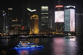 A brightly lit boat passes in front of the skyscrapers of Pudong in Shanghai, China