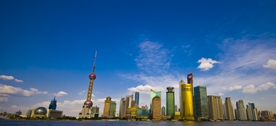 A panoramic view of the skyscrapers of Pudong, including the Oriental Pearl Tower, the Shanghai World Financial Center, and the Jin Mao Tower, under a blue sky in Shanghai, China