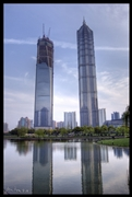 Two Pudong skyscrapers, the Shanghai World Financial Center (still under construction) and the Jin Mao Tower, stand side-by-side and are reflected in the water of a pond in Shanghai, China