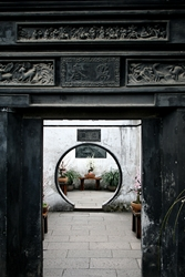 A view through a doorway decorated with an ornate frieze at Yuyuan Gardens in Shanghai, China
