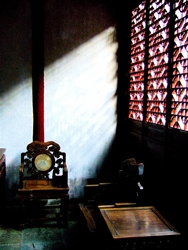 Slanted light rays pass through a window screen into a dim room decorated with traditional Chinese furniture at Yuyuan Gardens in Shanghai, China