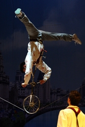 An acrobat riding a unicycle on his hands along a tightrope in a show in Shanghai, China
