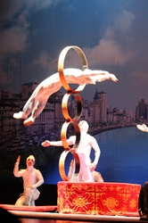 An acrobat jumping through a hoop high off the ground in a show in Shanghai, China