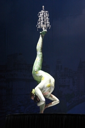 An acrobat standing on one foot while balancing glasses on her other foot in a show in Shanghai, China