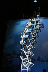 A tower of acrobats doing headstands on chairs balanced one on top of another in a show in Shanghai, China