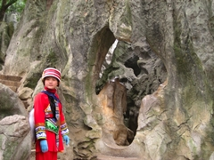 A tour guide from the Yi ethnic group stands next to a hole in a karst formation in the Stone Forest