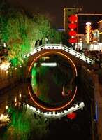A brightly lit bridge is reflected on the water of a canal in Suzhou (苏州), China
