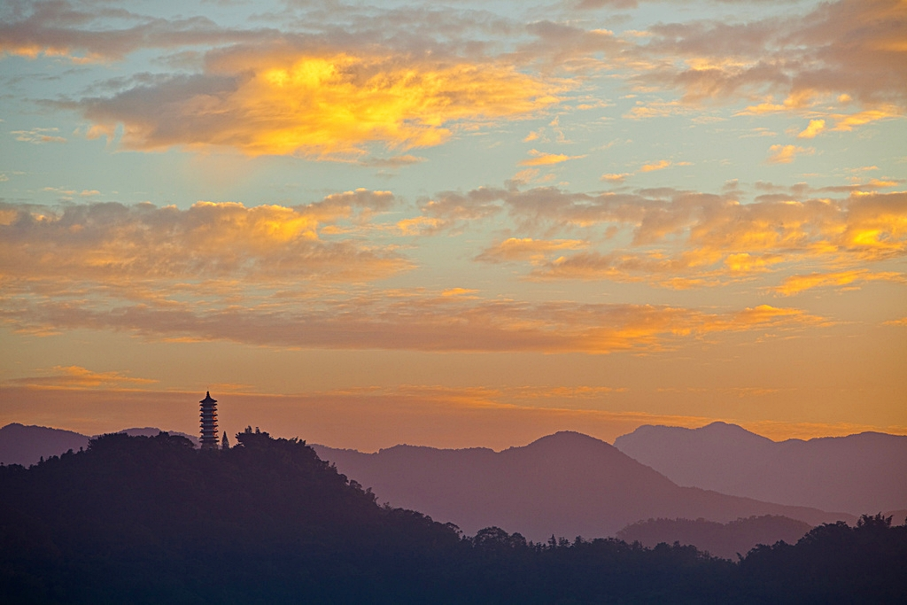 A distant pagoda on a hilltop at Taiwan's Sun Moon Lake during sunset