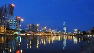 The brightly lit Saigon River and Ho Chi Minh City skyline at night
