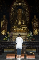 A visitor to a temple praying in front of a large golden Buddha statue at Big Goose Pagoda in Xi'an (西安), China