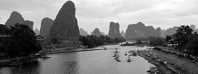 A black-and-white panoramic image of karst hills and bamboo rafts on the Yulong River (遇龙河) near Yangshuo (阳朔), China