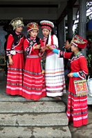 Women from the Tujia ethnic minority dressed in colorful red dresses, with ornately decorated hats, in Zhangjiajie (张家界), Hunan Province, China
