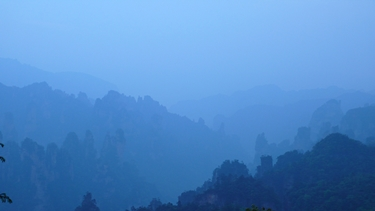 Karst landscape silhouetted in the misty blue predawn light of Zhangjiajie (张家界), Hunan Province, China