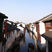 Gondolas pass between close-set houses on a canal in Zhouzhuang, China
